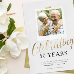 A 50th anniversary photo invitation with a gold envelope, surrounded by magnolias