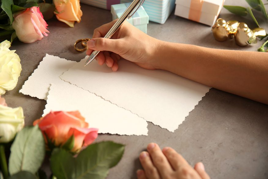 Canceling events because of coronavirus: A woman handwrites notes surrounded by flowers, wedding rings, and wedding gifts