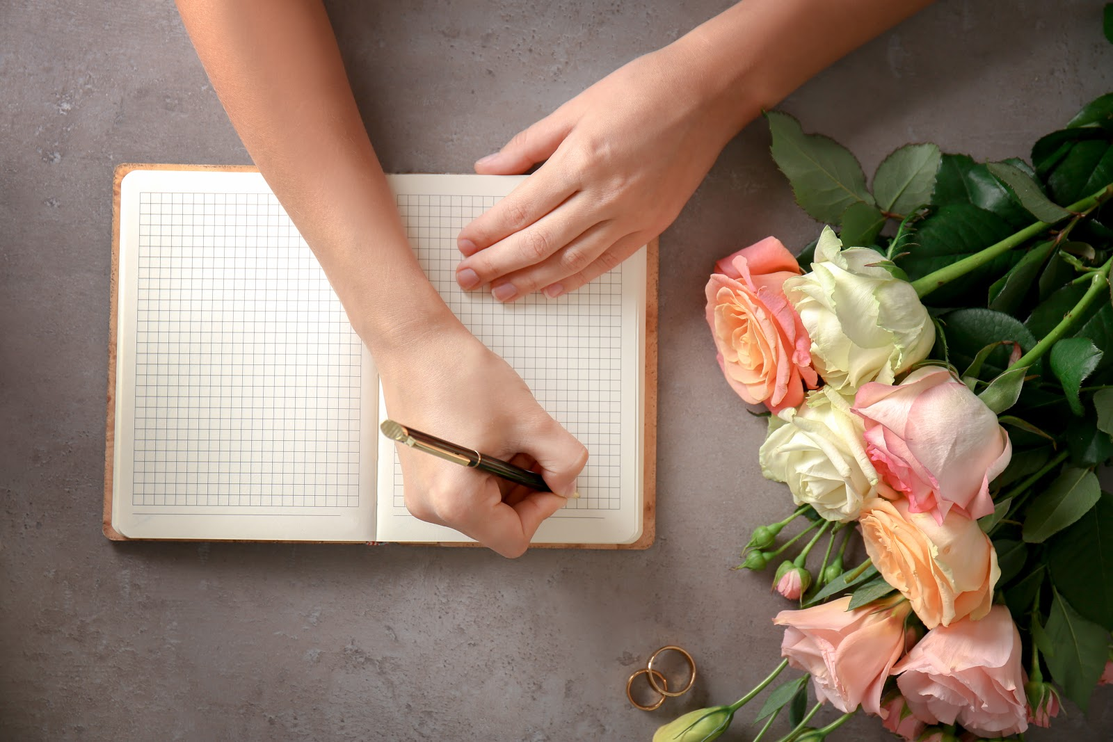 Wedding wishes: Roses and wedding rings next to hands that write notes in a notebook