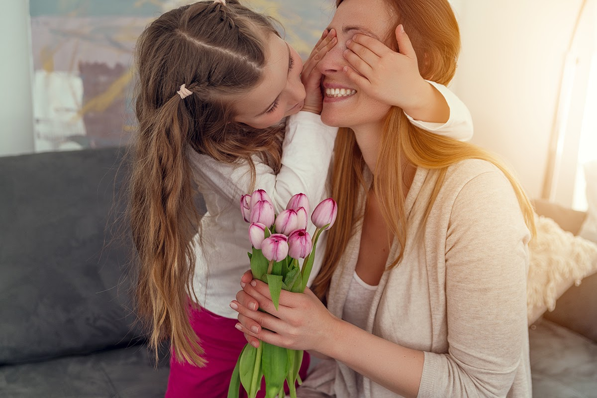 Mom holds tulips as daughter covers mom's eyes