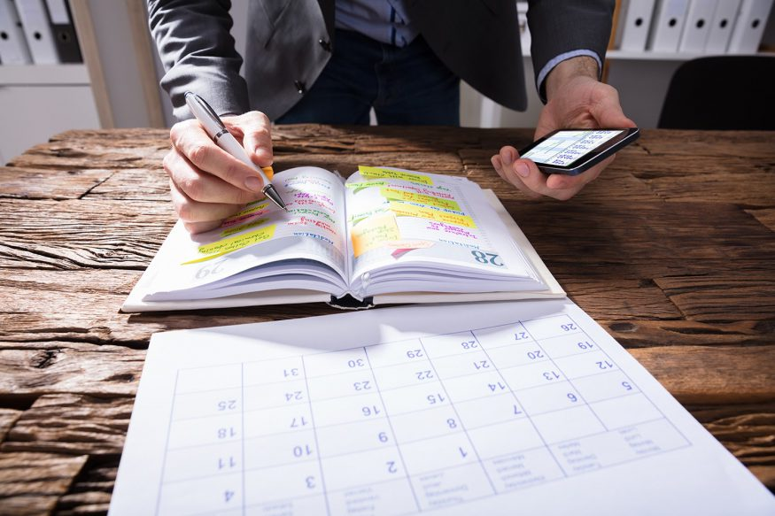 Canceling events because of coronavirus: A man with his planner, a calendar, a pen, and his phone
