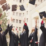College graduates throw their caps in the air