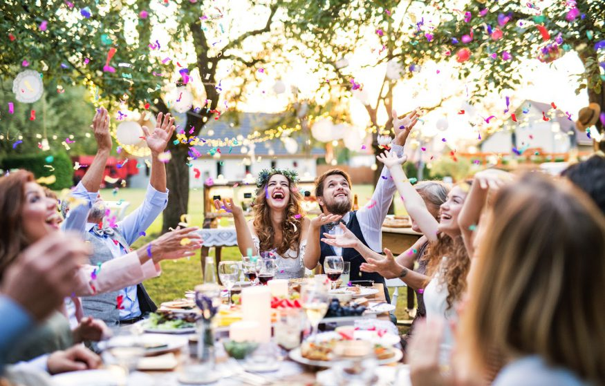 Wedding reception ideas: Guests throw confetti at an outdoor reception