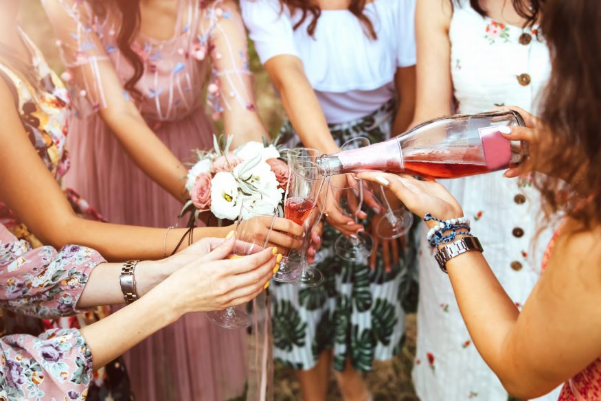 Bridal shower etiquette: A woman pours champagne into other women's glasses