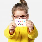 Thank you card ideas: A little girl holds up a handmade thank you card
