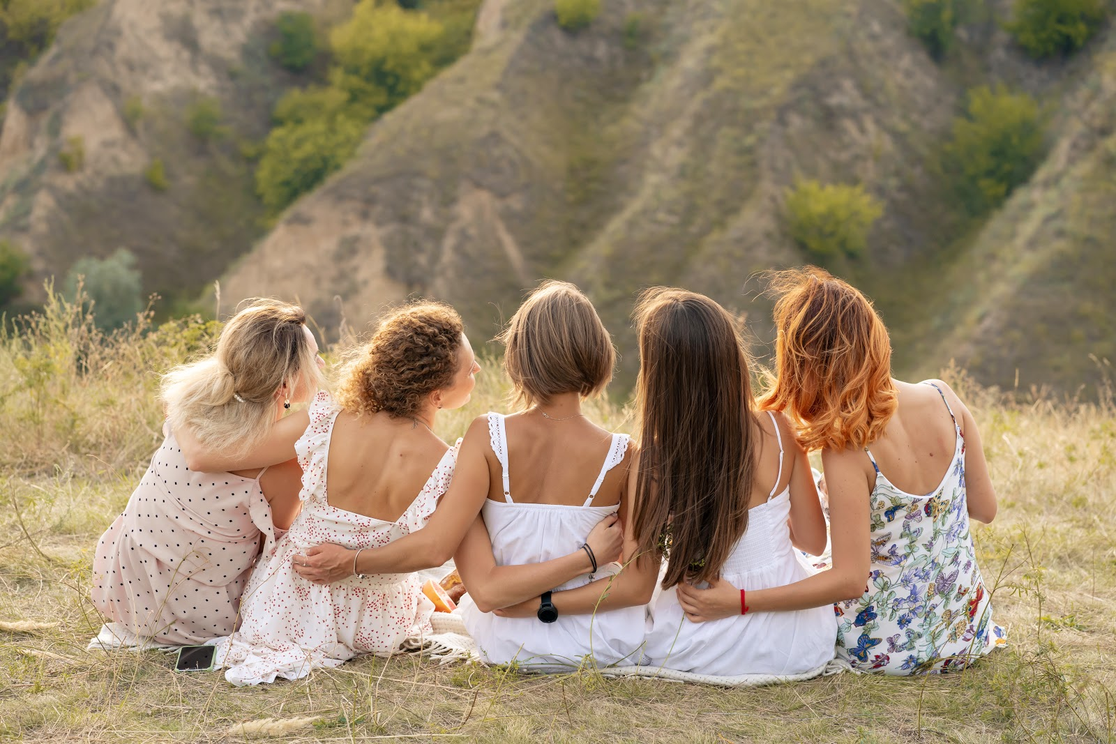 Bridal shower ideas: Five women sit on the grass wearing sun dresses