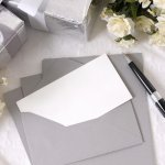 Wedding wishes: wedding gifts, flowers, and a blank note and pen next to an envelope
