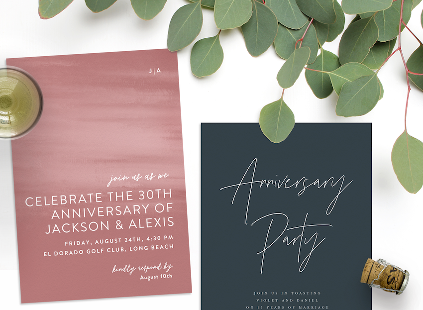 Two anniversary invitations with greenery, a glass of champagne, and a champagne cork