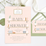 A baby shower invite next to a matching thank you card, surrounded by ribbon and baby's breath