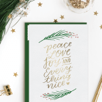 A Christmas card with classic Christmas card sayings surrounded by gold confetti stars and Christmas greenery