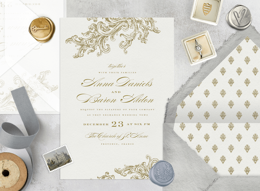 Formal wedding invitations laid out with an envelope, a wax seal, and an engagement ring