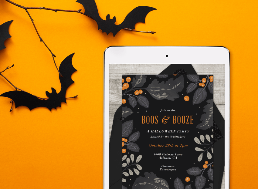 A digital halloween invitation on a tablet, surrounded by die-cut paper bats