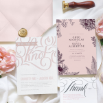 Three letterpress wedding invitations laid out on fabric with flowers, ribbons, and a wax seal