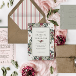 Rustic wedding invitations laid out with their envelopes and flowers