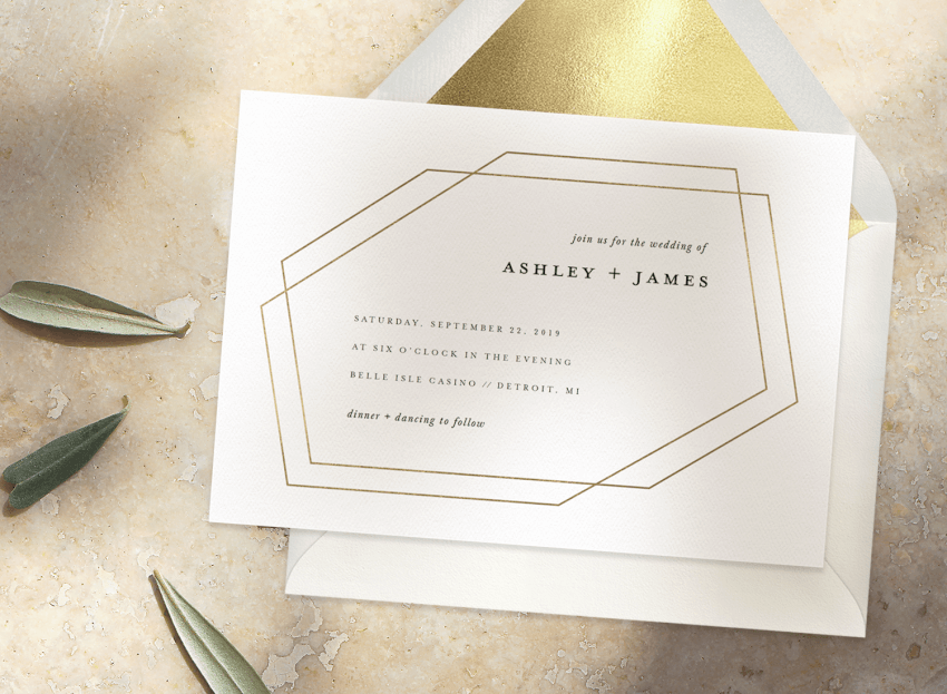 A white and gold, simple wedding invitation with an envelope