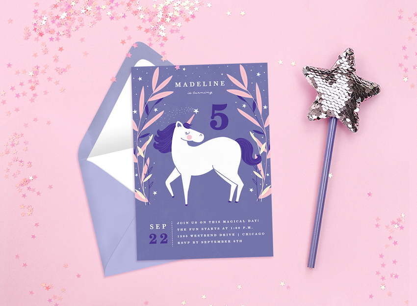 Unicorn invitations surrounded by pink glitter and a fairy wand