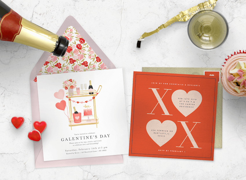 Valentine's Day cards with envelopes, surrounded by a champagne bottle and cupcake