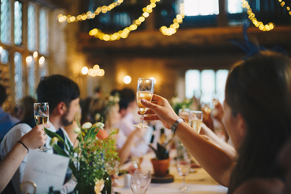 When to send wedding invitations: Guest's hold up their glasses to cheers at a wedding reception