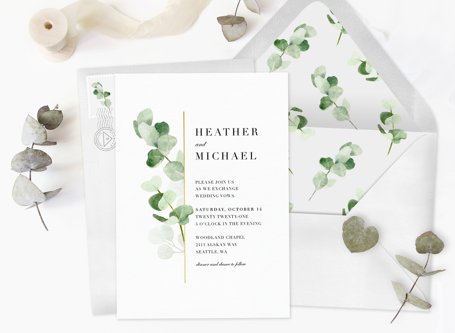 An all-in-one wedding invitation with a matching envelope, ribbon, and greenery
