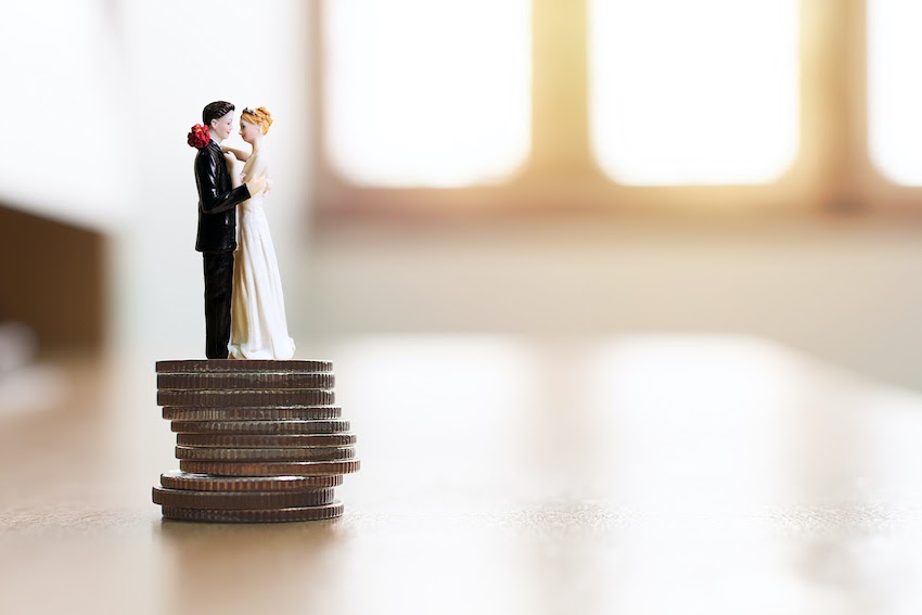 Average cost of wedding invitations: A bride and groom figurine stands on top of a stack of quarters