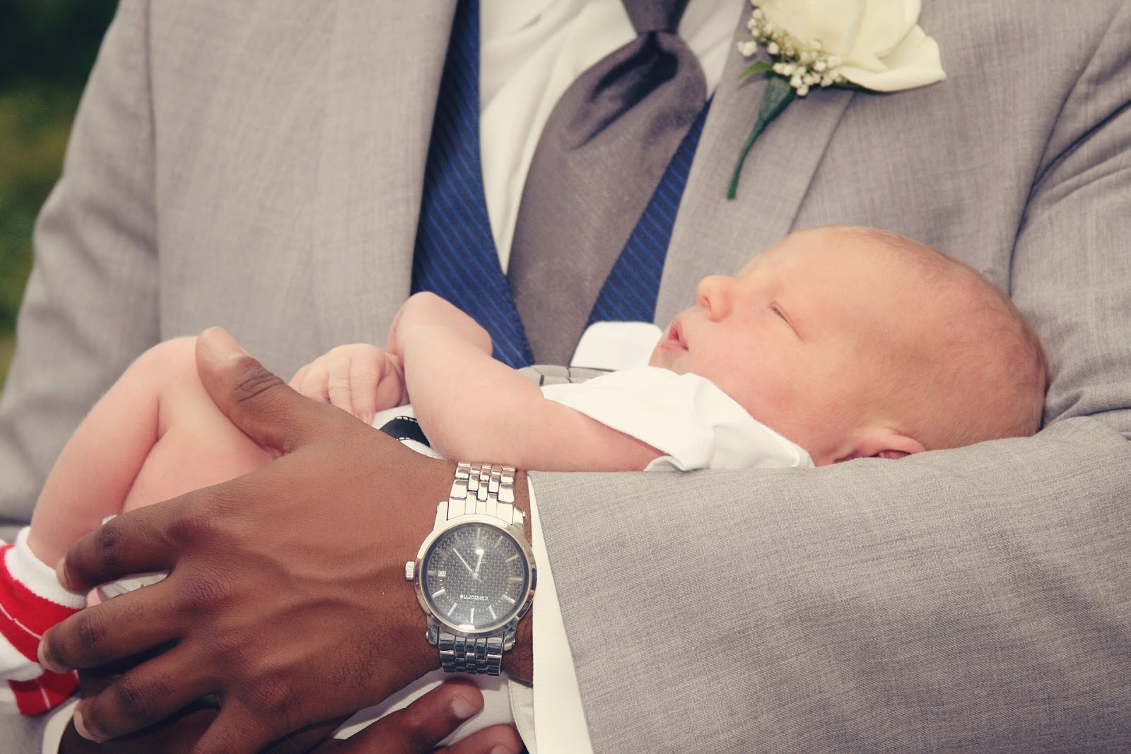 A man in a suit holds a baby