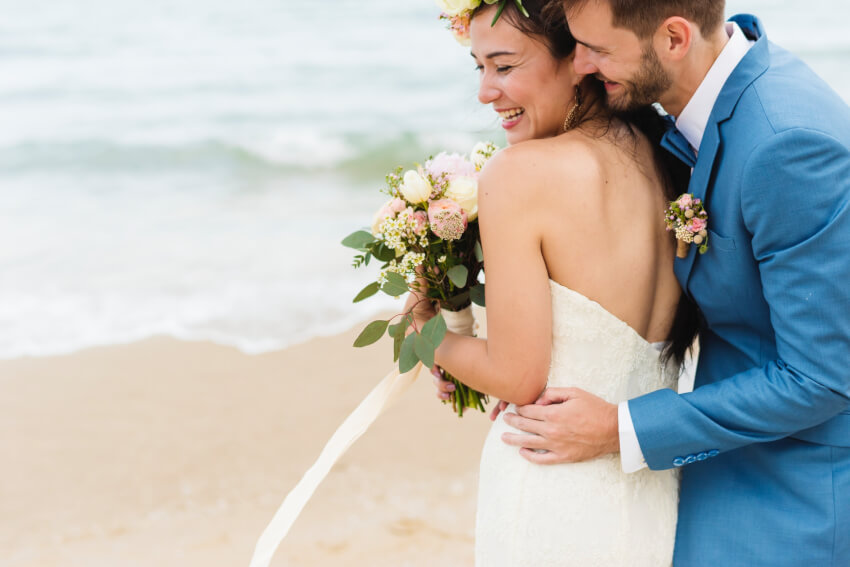 Beach wedding invitations: a smiling bride and groom on the beach