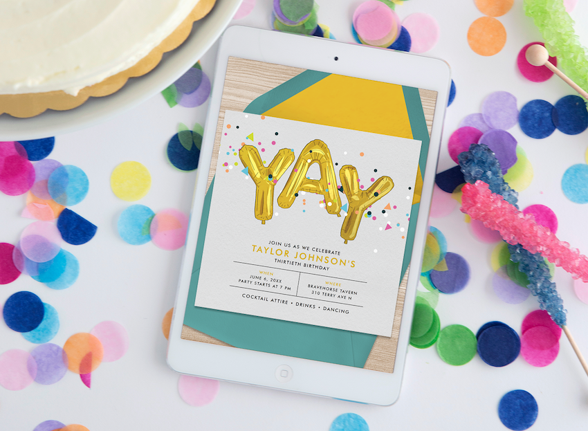 A tablet, surrounded by confetti and party decor, displays birthday invitations online