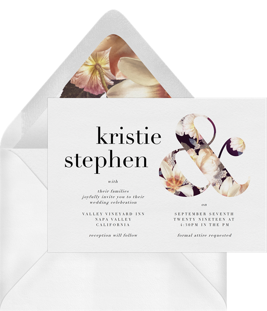 A wedding invitation with a floral ampersand and modern wedding invitation wording