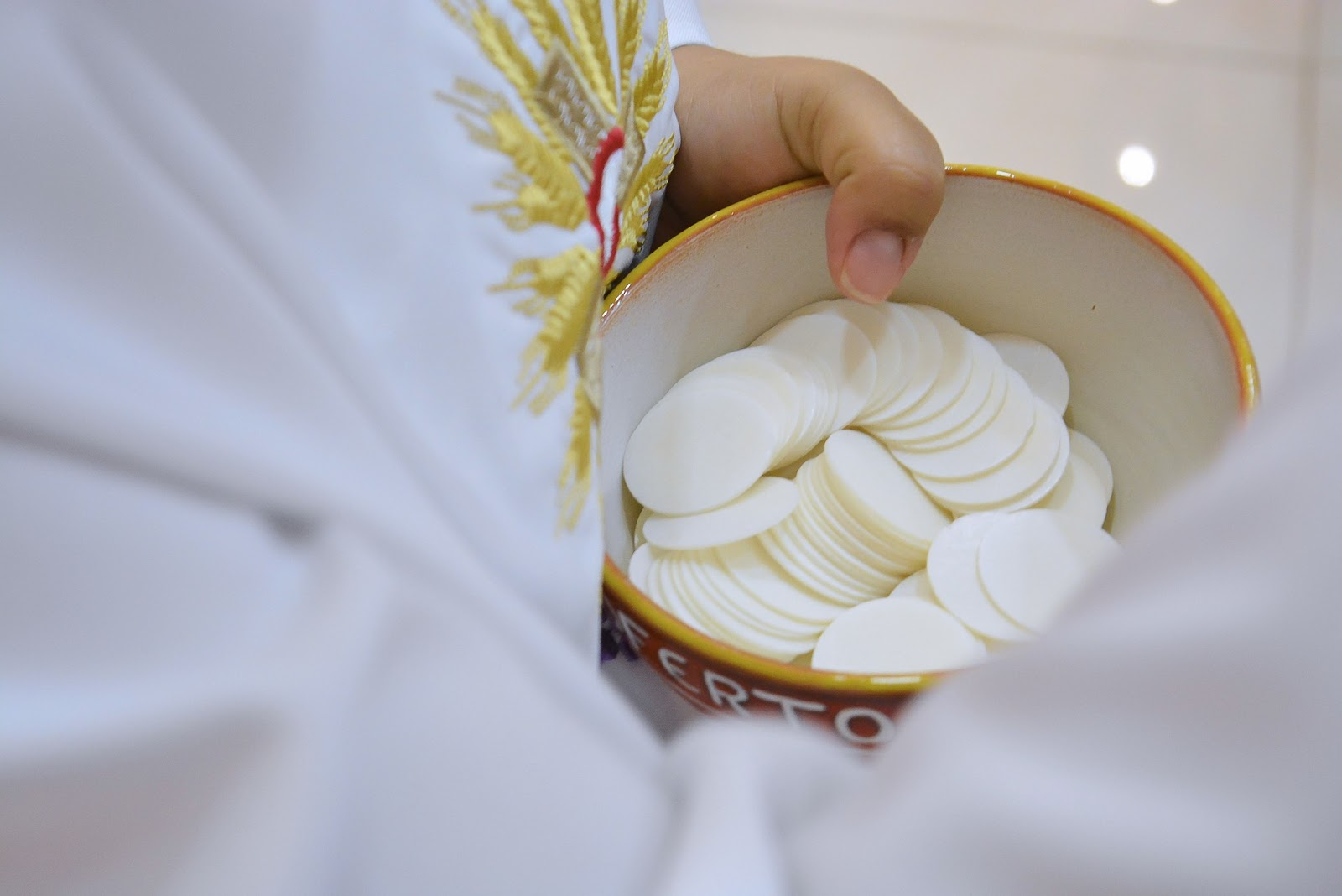A robed person holds communion wafers