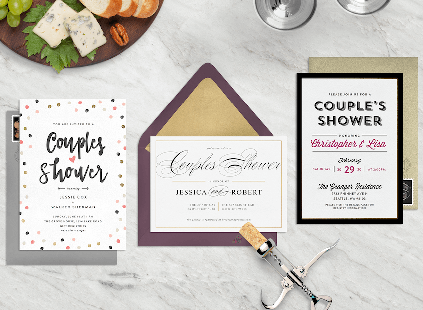 Three couple's shower invitations on a marble countertop with a wine cork and cheese board
