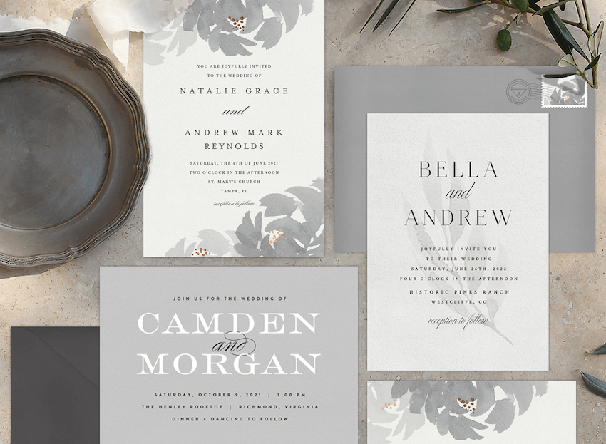 Three elegant wedding invitations laid out with greenery and fine china