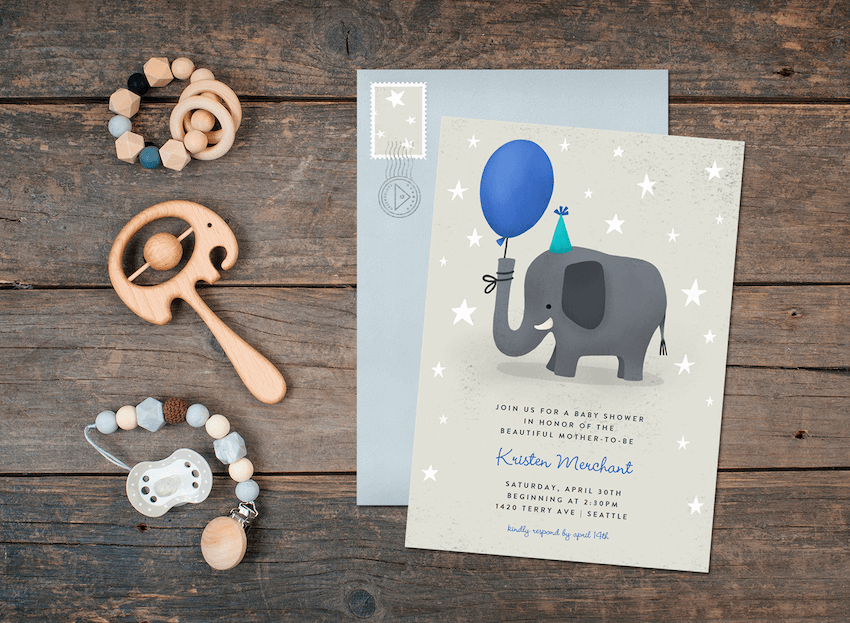An elephant baby shower invitation on a wood table with envelope and baby toys