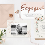Three engagement party invitations laid out with a wax-sealed envelope, greenery, and ribbon