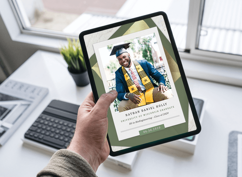 A hand holds a tablet with a college graduation announcement on the screen