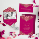 Three Indian wedding invitations laid out on a white table with fuchsia flowers