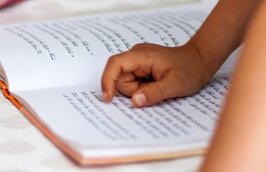 A child's hand points to the Torah