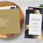 Two open house invitations with a spring of greenery and a wood trivet