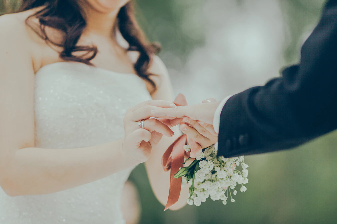 A bride puts a ring on a groom's finger
