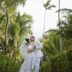A bride and groom kiss in a tropical setting