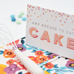 "Bridal shower invitation wording: A card reading ""any excuse to eat cake"" with a whisk and a floral napkin"