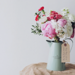 A pitcher of flowers with a gift tag featuring Mother's Day sayings