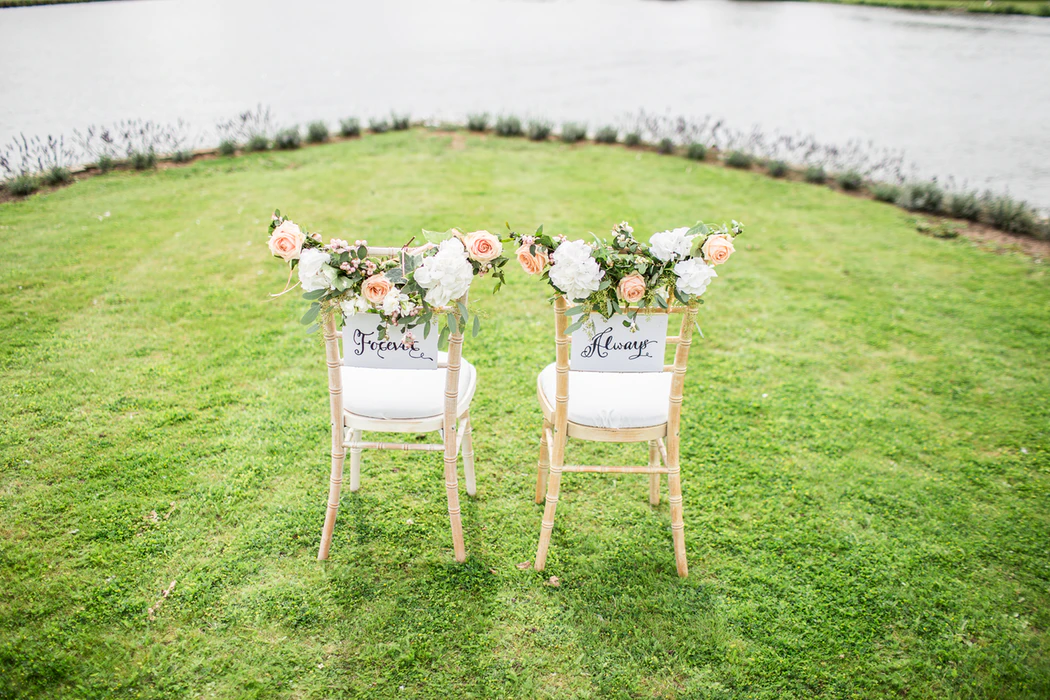"""Wedding words: two ceremony chairs decorated flowers and signs that read """"forever"""" and """"always"""""""