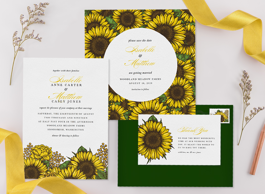 Three sunflower wedding invitations with an envelope, ribbon, and flower sprigs