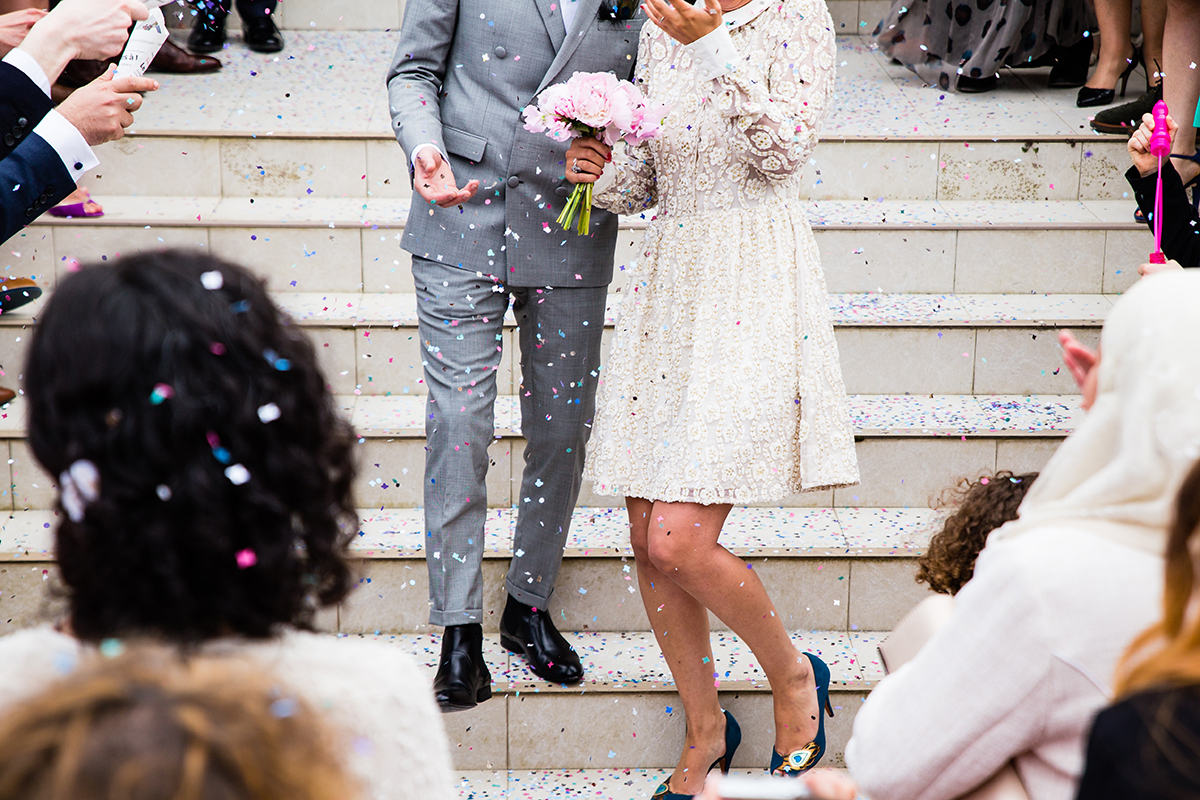 How to address wedding invitations: A wedding couple gets confetti thrown at them by their guests