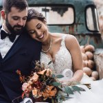 When to send save the dates: a bride and groom in the back of an antique truck