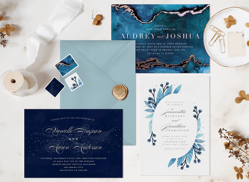 Blue and white winter wedding invitations surrounded by matching envelopes, stamps, and gold accents