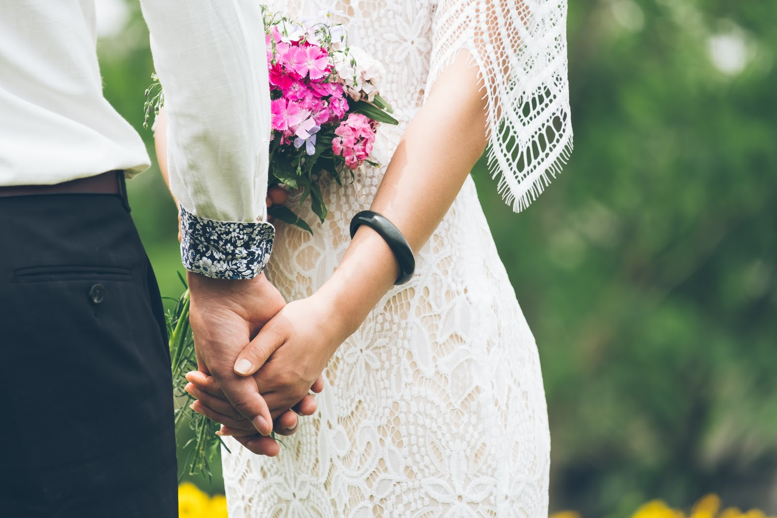 When to send save the dates: bride and groom hold hands